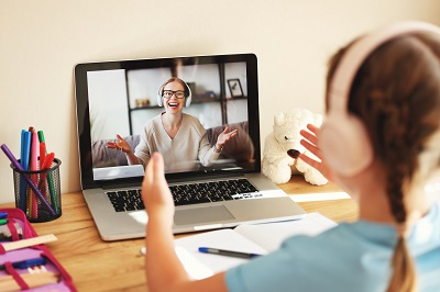 schoolgirl wearing headphones communicates via video call with an happy online teacher sitting at home